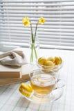 Una tazza di tè caldo, dei tulipani gialli, dei narcisi gialli, di vecchi libri e dei maccheroni del limone su un fondo leggero Immagini Stock
