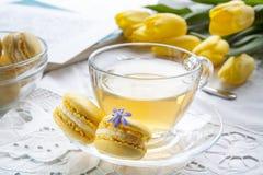 Una tazza di tè caldo, dei tulipani gialli, dello sketchbook e dei maccheroni del limone su un fondo leggero Fotografie Stock Libere da Diritti