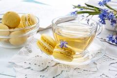 Una tazza di tè caldo, del bucaneve dei fiori, dello sketchbook e dei maccheroni blu del limone su un fondo leggero Fotografia Stock Libera da Diritti