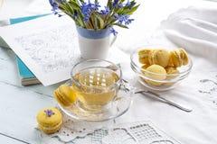 Una tazza di tè caldo, del bucaneve dei fiori, dello sketchbook e dei maccheroni blu del limone su un fondo leggero Fotografie Stock Libere da Diritti