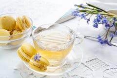 Una tazza di tè caldo, del bucaneve dei fiori, dello sketchbook e dei maccheroni blu del limone su un fondo leggero Immagini Stock