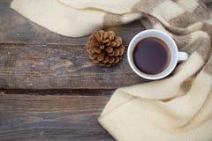 Una tazza di tè caldo e una sciarpa calda su un fondo di legno l piana fotografia stock