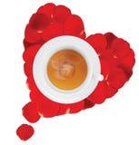 Una tazza di tè caldo nel cuore dei petali rosa Fotografie Stock
