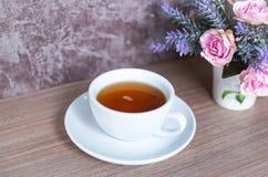Una tazza di tè cinese sulla tavola di legno Bevanda per sano con il fiore rosa in vaso immagini stock