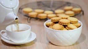 Una tazza di tè con i biscotti stock footage