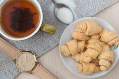 Una tazza di tè con il forno ed orologio sul fondo della tela e di legno Installazione di mattina immagini stock