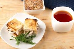 Una tazza di tè con il mini panino del pane tostato del pollo Fotografia Stock Libera da Diritti