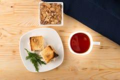 Una tazza di tè con il mini panino del pane tostato del pollo Fotografia Stock