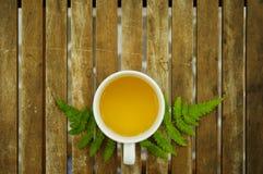 Una tazza di tè con la foglia verde sulla tavola di legno Immagini Stock Libere da Diritti
