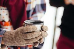 Una tazza di tè da un termos sull'inverno fa un picnic nel legno ` S della mano della donna in guanti caldi Immagini Stock Libere da Diritti