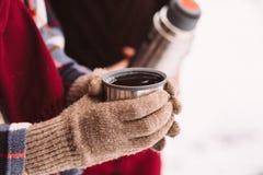 Una tazza di tè da un termos sull'inverno fa un picnic nel legno ` S della mano della donna in guanti caldi Immagine Stock Libera da Diritti