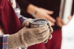 Una tazza di tè da un termos sull'inverno fa un picnic nel legno ` S della mano della donna in guanti caldi Fotografia Stock Libera da Diritti
