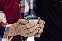 Una tazza di tè da un termos sull'inverno fa un picnic nel legno ` S della mano della donna in guanti caldi Fotografia Stock
