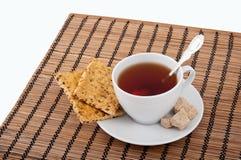 Una tazza di tè, di uno zucchero marrone e dei cracker Immagini Stock Libere da Diritti