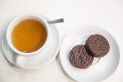 Una tazza di tè e dei biscotti sulla tavola nel fondo bianco immagine stock