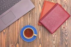 Una tazza di tè e due taccuini con un computer portatile su una tavola di legno Piccola profondità di campo fotografia stock