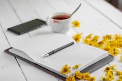 Una tazza di tè e un blocco note con la penna fotografia stock libera da diritti