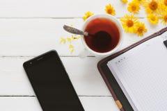 Una tazza di tè e un blocco note con la penna fotografie stock libere da diritti