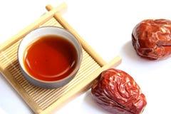 Una tazza di tè nero con le date rosse Fotografia Stock Libera da Diritti