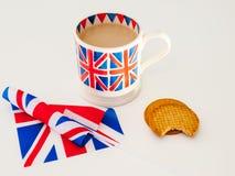 Una tazza di tè e dei biscotti inglesi con una bandiera Fotografie Stock