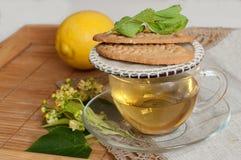 Una tazza di vetro del tè del fiore della calce, dei biscotti e di un limone maturo su una superficie di legno Immagine Stock