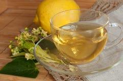 Una tazza di vetro del tè del fiore della calce, dei biscotti e di un limone maturo su una superficie di legno Fotografia Stock