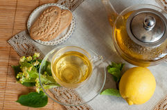 Una tazza di vetro del tè e dei biscotti del fiore della calce su una superficie di legno con un tovagliolo di tela del pizzo Fotografia Stock