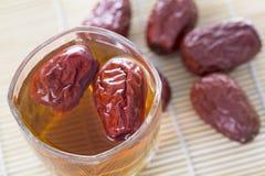 Una tazza di vetro del tè rosso cinese della data sulla tavola Immagini Stock