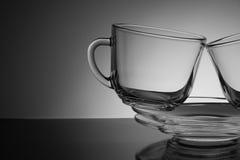 Una tazza due di vetro per tè e un piattino vuoto su un fondo nero Fotografia Stock Libera da Diritti