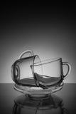 Una tazza due di vetro per tè e un piattino vuoto su un fondo nero Fotografie Stock Libere da Diritti