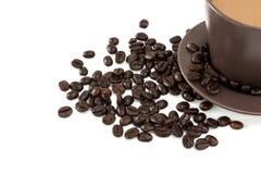 Una tazza e chicchi di caffè sopra Fotografie Stock Libere da Diritti