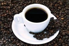 Tazza di caffè nero sui fagioli Fotografia Stock Libera da Diritti