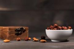 Una tazza piena dei dadi, delle nocciole e di un cofanetto di legno Immagine Stock Libera da Diritti