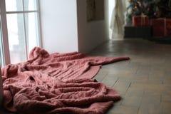 Una tela escocesa marrón hecha punto miente cerca de la ventana imagen de archivo libre de regalías