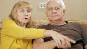 Una televisión de observación de los pares mayores en casa en el sofá Las selecciones de risa TV teledirigidas sí mismo de la muj almacen de video