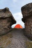 Una tenda arancio sta alta nelle montagne fra due alte rocce Immagine Stock Libera da Diritti