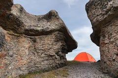 Una tenda arancio sta alta nelle montagne fra due alte rocce Immagine Stock