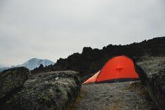 Una tenda arancio sta alta nelle montagne fra due alte rocce Immagini Stock