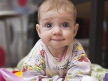 Un bambino di sei mesi con un divertimento guarda a casa Fotografia Stock