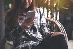 Una tenencia asiática hermosa de la mujer, usando y mirando el teléfono elegante mientras que se sienta en al aire libre Imagen de archivo libre de regalías