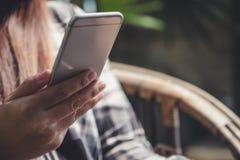 Una tenencia asiática hermosa de la mujer, usando y mirando el teléfono elegante mientras que se sienta en al aire libre Imágenes de archivo libres de regalías