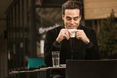 Una tenencia de consumición de la taza de café del hombre feliz joven Imagen de archivo libre de regalías