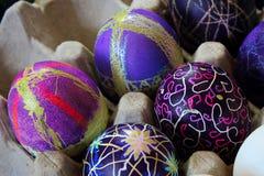 Una tenencia del cartón del huevo adornó los huevos de Pascua Foto de archivo
