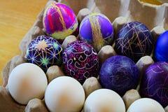 Una tenencia del cartón del huevo adornó los huevos de Pascua Imagenes de archivo