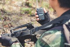 Una tenencia del soldado y una radiocomunicación armadas con en el campo de batalla Foto de archivo libre de regalías