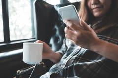 Una tenuta asiatica della donna, per mezzo e toccando di uno Smart Phone mentre bevendo caffè Fotografia Stock Libera da Diritti