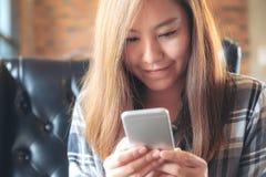 Una tenuta asiatica della donna, utilizzando ed esaminando Smart Phone nel caffè Fotografie Stock Libere da Diritti