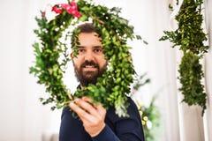 Una tenuta dell'uomo dei pantaloni a vita bassa ed osservare attraverso una corona verde il tempo di Natale immagine stock