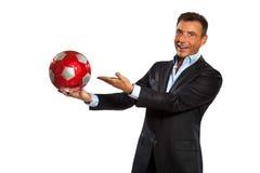 Una tenuta dell'uomo di affari che mostra un pallone da calcio Immagine Stock