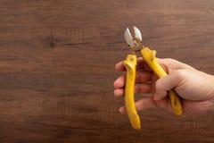Una tenuta dell'uomo una pinza gialla di taglio su fondo di legno Fotografia Stock